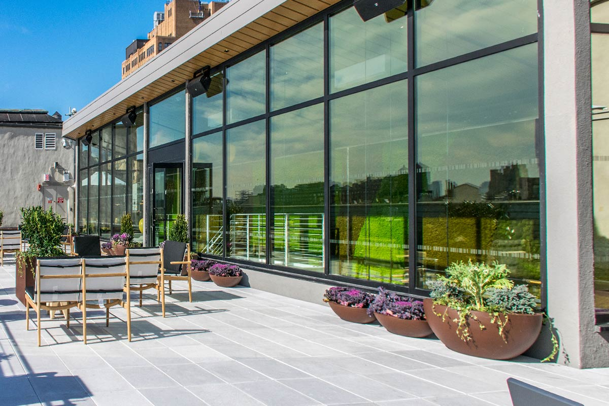 A New York rooftop terrace features a glass-walled pavilion at the Anheuser-Busch InBev offices built by general contractor J.T. Magen & Company Inc.