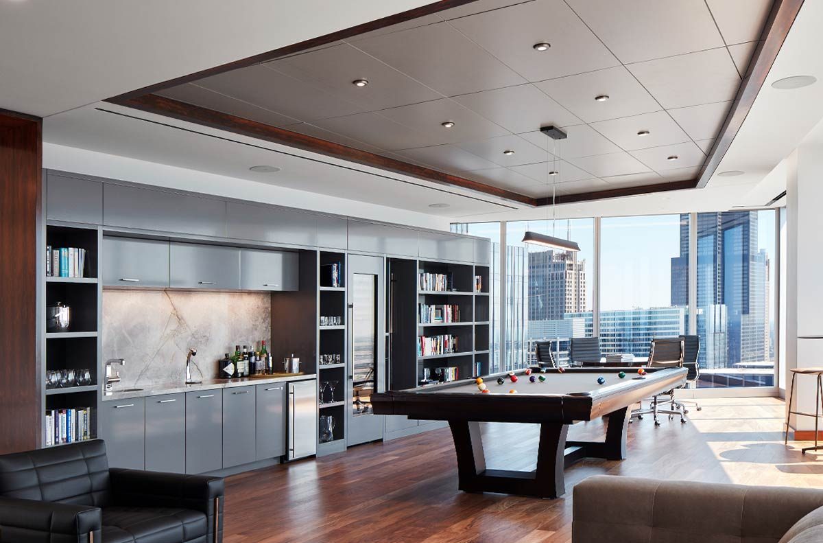 Completed office break room with mini-bar, snooker table, library, relaxed seating and Chicago skyline views at Balyasny Asset Management's office built by J.T. Magen & Company Inc.