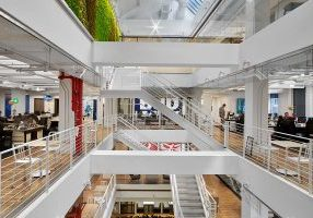 Five-floor atrium framed with white staircases, beams and steel railings connects the J.T. Magen-built open-plan offices of Anheuser-Busch InBev in Chelsea.