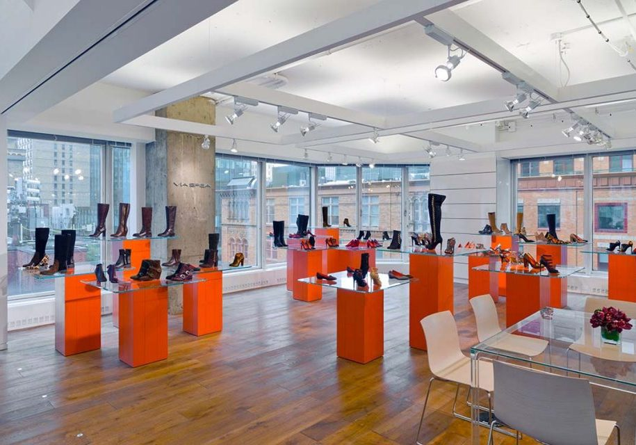 Trade showroom with Brown Shoe's latest range of footwear displayed glass tabletops supported by chunky orange bases at their office built by J.T. Magen on Barclay Street, New York.