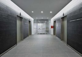 Two-tone elevator lobby with light grey tiled flooring and a dark grey laminate wall finish at the Chadbourne & Parke office built by J.T. Magen on Avenue of the Americas, New York.