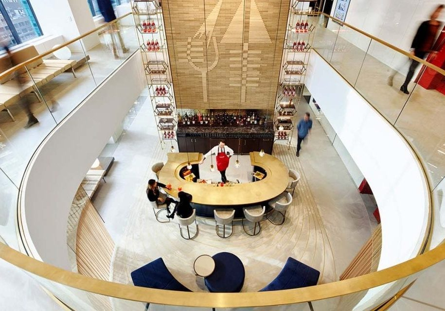 An atrium bar with a 16-foot cerused oak feature wall and a curved mezzanine-style platform overlooking the center of the bar at the Campari Group headquarters in the Grace Building, New York built by J.T. Magen.