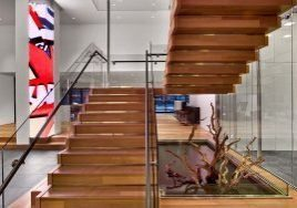 A wooden based U-shaped stairs framed with glass paneling and steel rails at the Constituency Management Group headquarters built by J.T. Magen on Third Avenue, New York.
