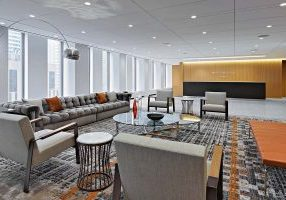 Reception and waiting area with a range of light-grey couches and armchairs arranged around a central coffee table alongside the reception desk at Mayer Brown's Rockfeller Center headquarters built by general contractor J.T. Magen & Company Inc. on Avenue of the Americas, New York.