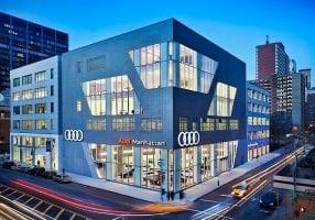 Two silver buildings, each with different window configurations, house the Volkswagen and Audi Manhattan dealerships built by J.T. Magen & Company Inc. on Eleventh Avenue, New York.