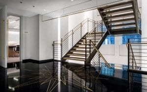 Black terrazzo flooring with a starburst motif leads to a U shaped staircase at the Creative Arts Agency office built by J.T. Magen in the Chrysler Building, New York.